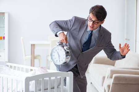Young businessman trying to work from home caring after newborn baby