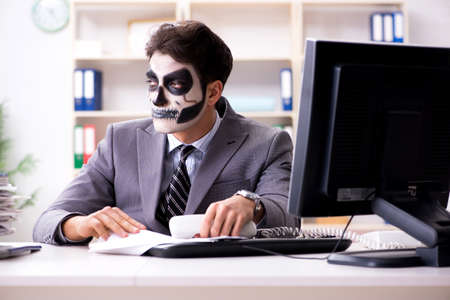 Businessmsn with scary face mask working in office Фото со стока