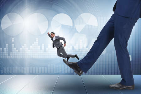 Bad angry boss kicking employee in business concept Stok Fotoğraf