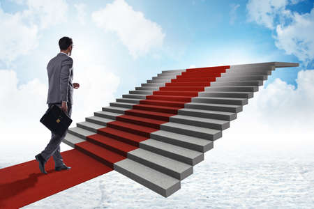 Young businessman climbing stairs and red carpet into sky Foto de archivo