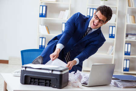 Businessman angry at copying machine jamming papers Stock Photo - 96821345