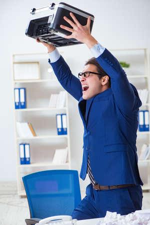 Empresario enojado con copiadora atascando papeles Foto de archivo