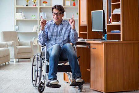 Disabled student studying at home on wheelchair Stock Photo