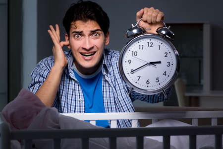 Young father under stress due to baby crying at night