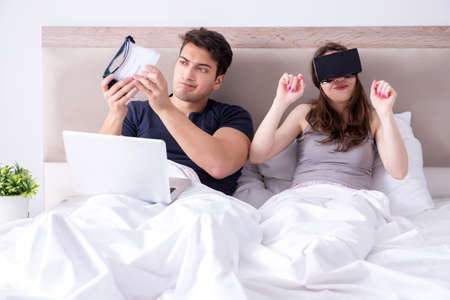 Wife and husband with virtual reality goggles in the bed
