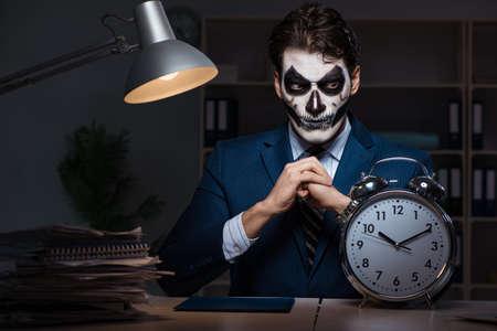 Uomo d'affari con la maschera di protezione spaventosa che lavora tardi nell'ufficio