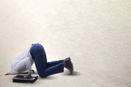 Businessman hiding his head in sand escaping from problems Stock Photo