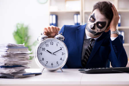 Businessman with scary face mask working in office Banque d'images
