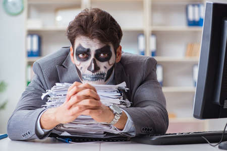 Businessman with scary face mask working in office Imagens