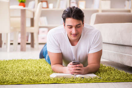 Man reading book at home on floor