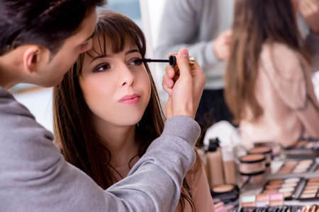 Man doing make-up for cute woman in beauty salon Imagens
