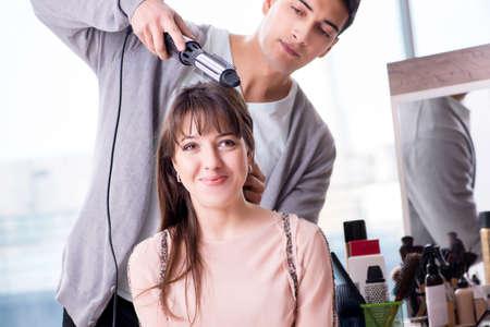 Man stylist working with woman in beauty salon Foto de archivo