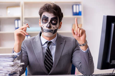 Businessmsn with scary face mask working in office Stock Photo