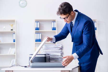 Businessman making copies in copying machine Standard-Bild