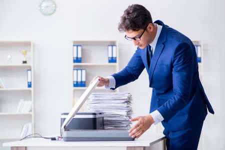 Businessman making copies in copying machine Banque d'images