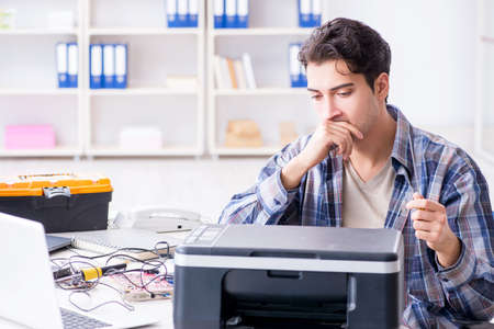 Hardware repairman repairing broken printer fax machine 版權商用圖片