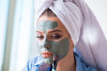 Woman applying clay mask with brush at home