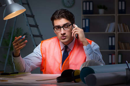 Construction architect working on drawings late at night Stock Photo