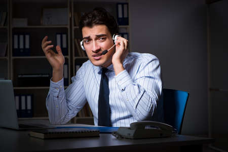 Tired and exhausted helpdesk operator during night shift Stock Photo