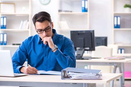Hübscher Geschäftsmannangestellter, der an seinem Schreibtisch im Büro sitzt