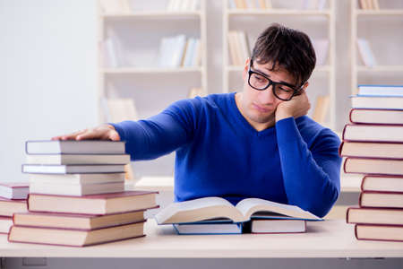Male student preparing for exams in college library Imagens - 98106294