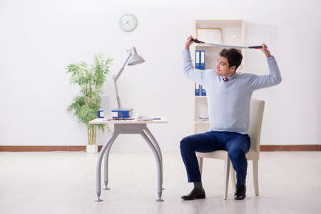 Man exercising with elastic band in office during lunch break
