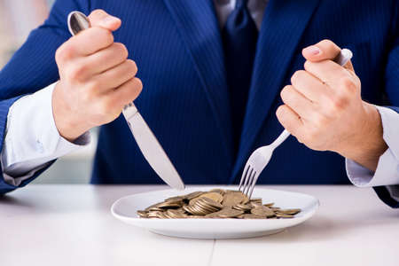 Funny businessman eating gold coins in office Stock Photo