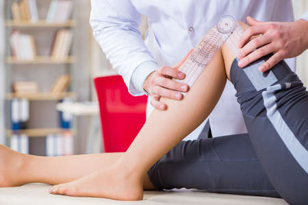 Doctor checking patients joint flexibility Stock Photo