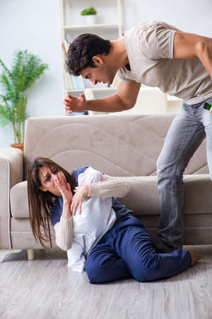 Desparate wife with aggressive husband in domestic violence conc Stock Photo