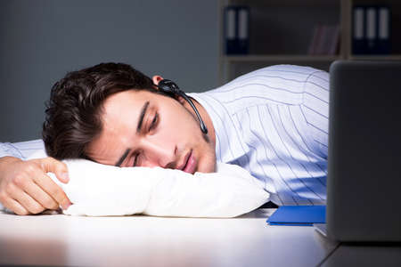Tired and exhausted helpdesk operator during night shift Stockfoto
