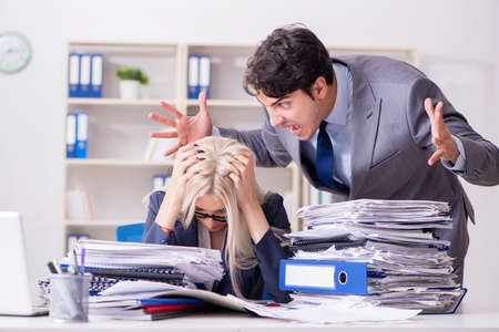 Angry irate boss yelling and shouting at his secretary employee Imagens