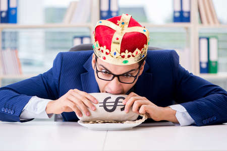 King businessman with money sack in office