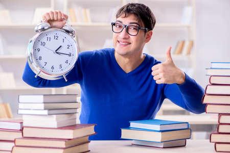 Étudiant de sexe masculin se préparant aux examens dans la bibliothèque du collège Banque d'images