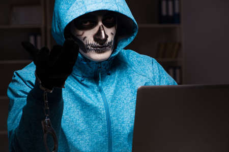 Scary hacker hacking security firewall late in office