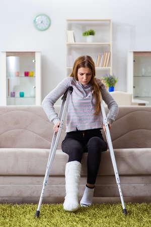Mujer joven con pierna rota en casa