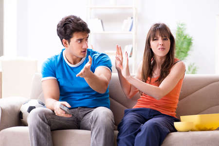 Young man watching football with his wife at home