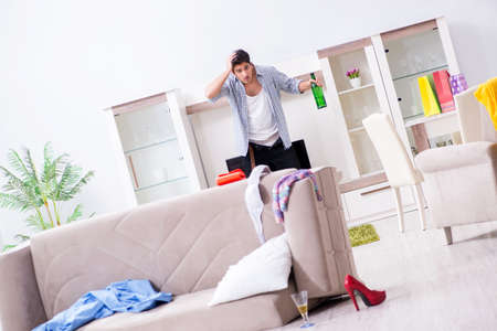 Man with mess at home after house party Stock fotó