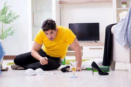 Man with mess at home after house party Stock Photo