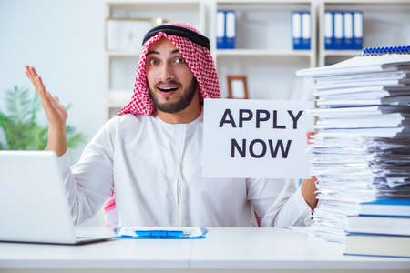 Arab man sitting at desk with message Stock Photo
