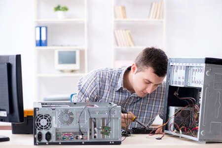 Young technician repairing computer in workshop