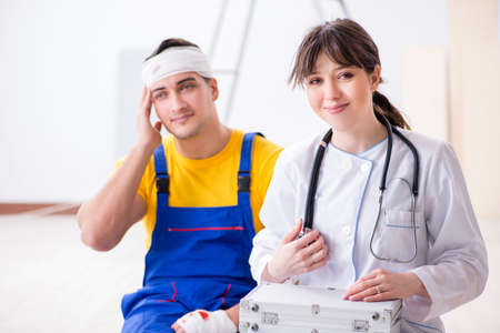 Worker with injured head and doctor Stockfoto