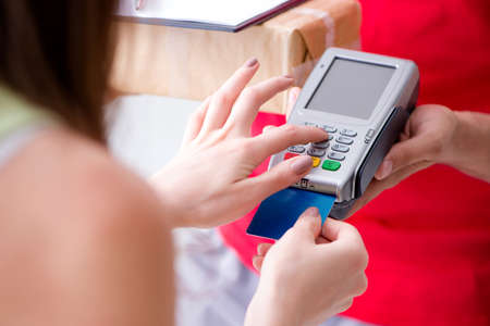 Parcel delivery being paid with pos and credit card Stock Photo