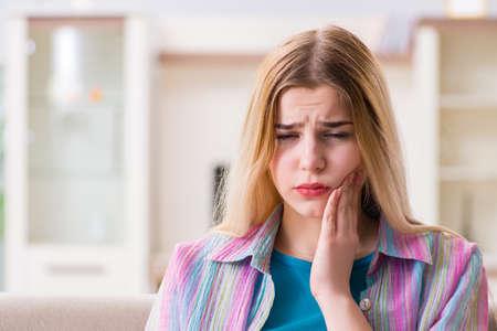 Junge Frau, die mit Schmerzen zu Hause leidet