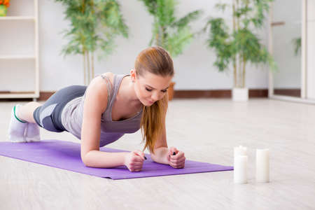 Young woman exercising in sports hall in healthy concept Stock Photo