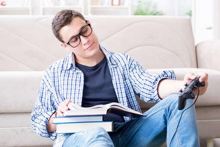 Jeune étudiant essayant d'équilibrer étudier et jouer à des jeux Banque d'images