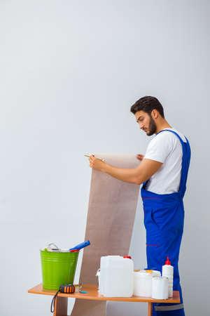 Worker working on wallpaper during refurbishment