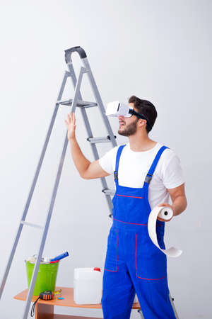 Man with VR glasses gluing wallpaper