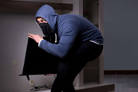 Burglar thief stealing tv from apartment house