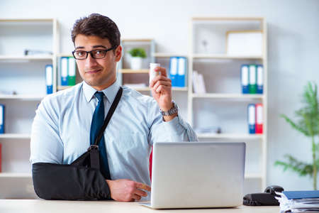 Businessman with broken arm working in office