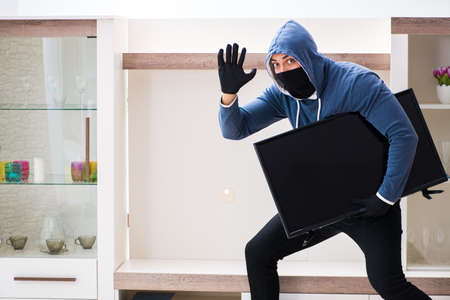 Man burglar stealing tv set from house Stock Photo